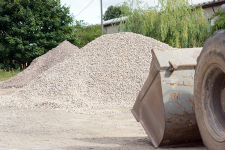 wheel loader: large wheel loader and a pile of stones Stock Photo