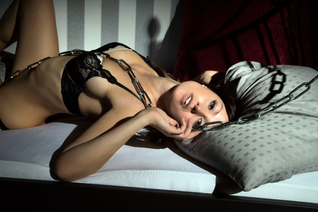 mujeres desnudas: mujer sexy en ropa interior acostada en la cama con una cadena de acero