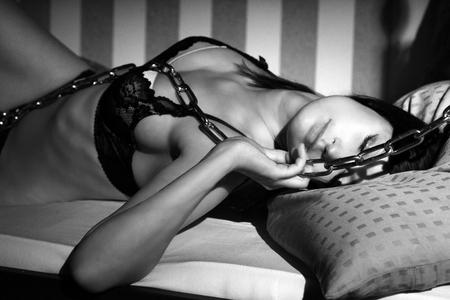 mujeres eroticas: mujer sexy en ropa interior acostada en la cama con una cadena de acero en blanco y negro