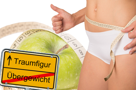 belly band: sign with the german words dream figure and overweight and a woman with measure tape Stock Photo