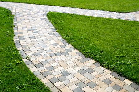 empedrado: ruta pavimentada y prado verde