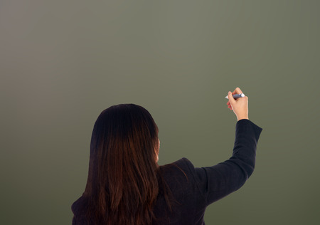 Woman writing on a empty chalkboard background photo