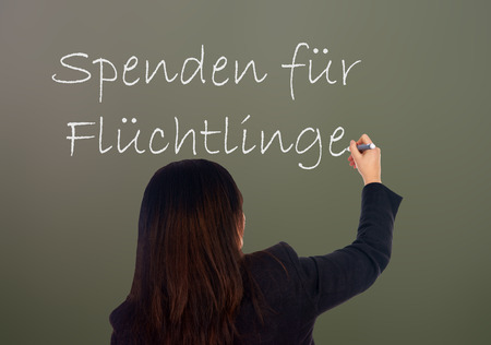 Woman writes the german words Donations for Refugees photo