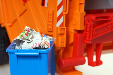 garbage truck: blue paper bin with paper waste in front of a garbage Truck