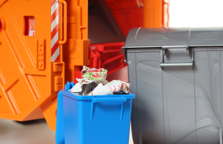 discard: blue paper bin with paper waste in front of a garbage Truck
