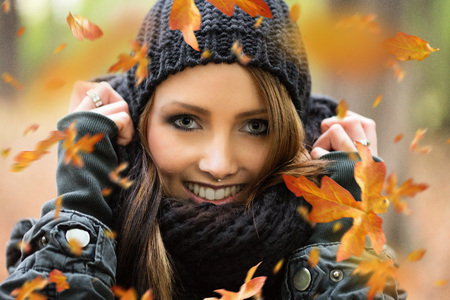 pretty woman in the autumn forest with flying autumn leaves