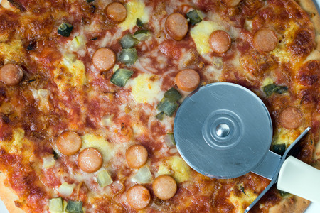 pizza cutter: Pizza topped with sausage, vegetables and cheese with a Pizza Cutter Stock Photo