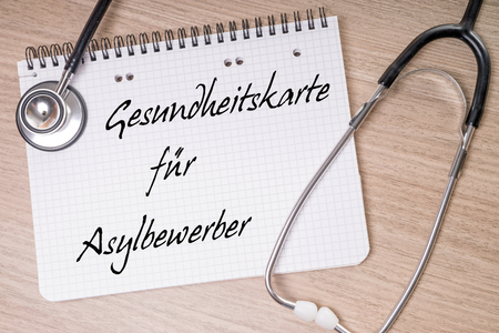seekers: Stethoscope and note with the German words health card for asylum seekers Stock Photo