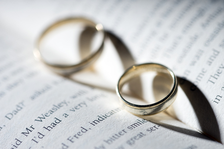reading material: Book with two Rings and heart shadow Stock Photo