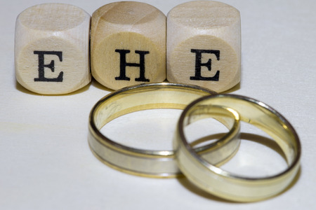 affiliation: two wedding rings with wooden cubes with the german word marriage