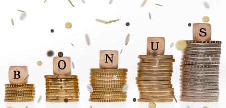 remuneraciones: Pila de monedas y dados de madera con la palabra bono