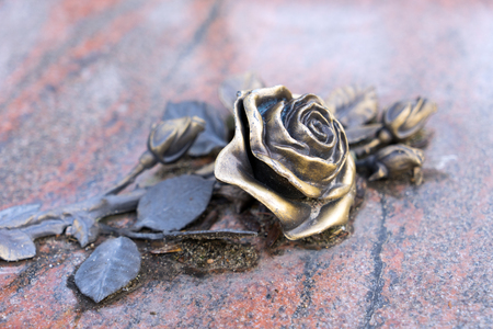 bereavement: golden rose on a grave stone Stock Photo