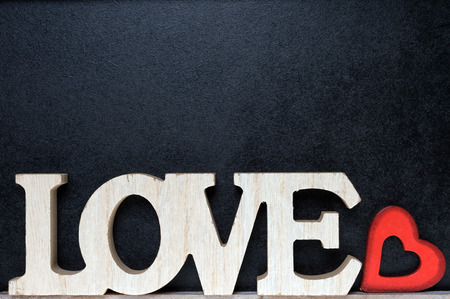 cordial: Wooden blackboard with wooden letters and the word Love and little red heart