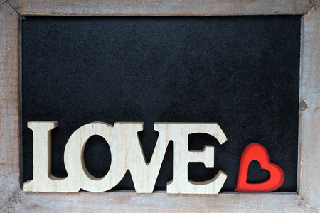 exempted: Wooden blackboard with wooden letters and the word Love and little red heart