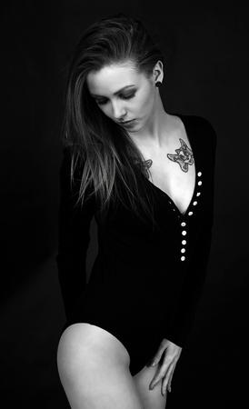 Frau in einem Bodysuit vor einem dunklen Hintergrund Standard-Bild - 55593999