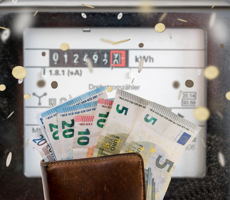 electricity prices: electricity meters and a wallet with euro banknotes and coins