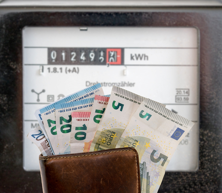 electricity prices: electricity meters and a wallet with euro banknotes