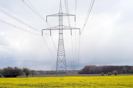 electricity tariff: electricity pylon and yellow rapefield Stock Photo