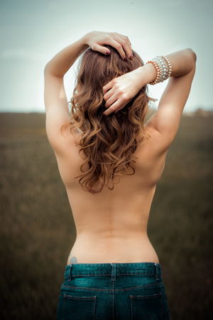 half naked: pretty woman standing half naked in a field