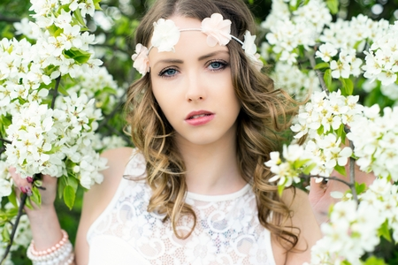 Pretty woman with flower hair band in front of a blossoming apple pretty woman with flower hair band in front of a blossoming apple tree stock photo mightylinksfo