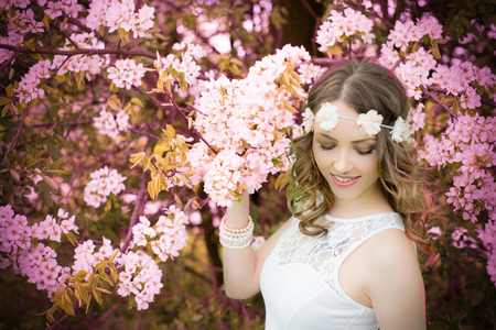 harbinger: pretty woman with flower hair band in front of a blossoming apple tree