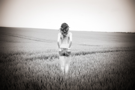 half naked: pretty woman standing half naked in a field in black and white Stock Photo