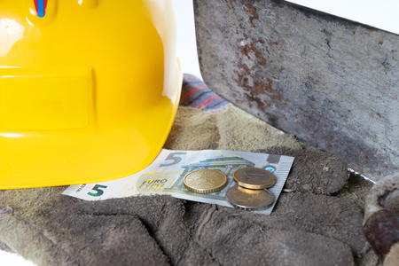 remuneration: Brick trowel with work gloves and eight euro fifty Stock Photo