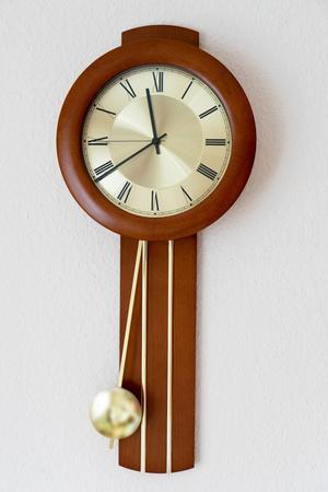 reloj de pendulo: Reloj con péndulo que cuelga en una pared