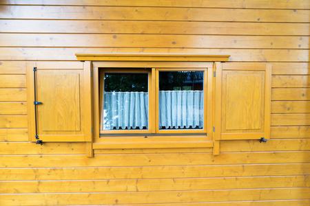 Log huis met ramen en luiken Stockfoto