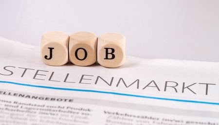 hartz 4: Daily newspaper with the german word job market and wooden cubes with the word job Stock Photo