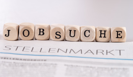 hartz 4: daily newspaper with the german word job market and wooden cubes with the german word job search