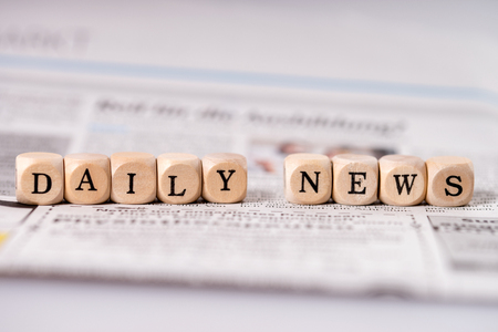 Daily newspaper and small wooden cubes with the words Daily News