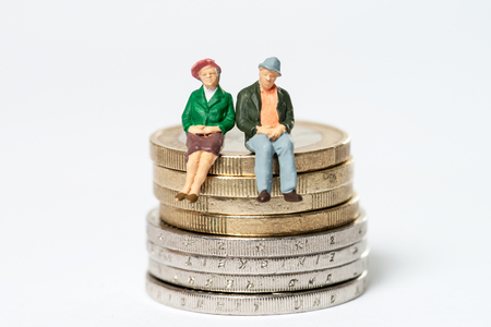 Retired  elderly couple sitting on euro coins