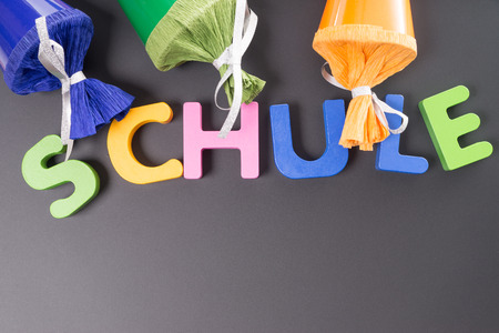 Sugar cones and colorful wooden letters with the german word school Stock fotó