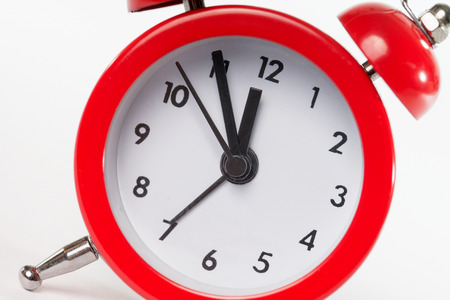 red alarm clock with time five to twelve