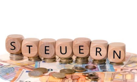 Holzwürfel mit dem deutschen Wort Steuern und Euro-Geld