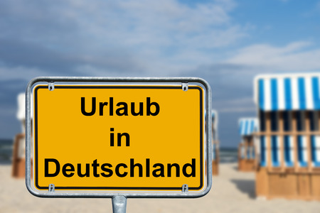 Beach chairs and town sign with the German words holiday in Germany Stock Photo