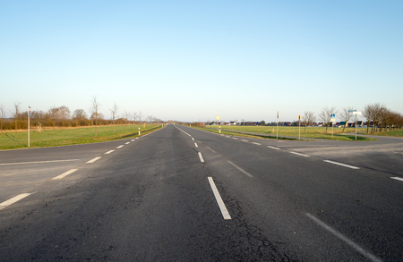 Road with marker stripes and blue sky in germany Standard-Bild - 100717084
