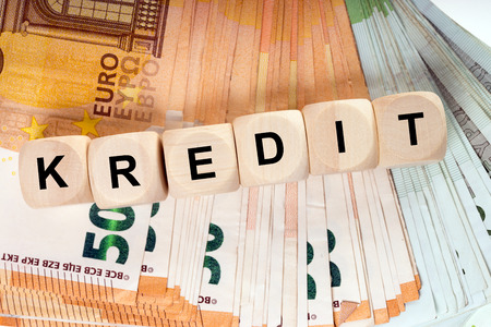 many euro banknotes and wooden cubes with the german word credit Standard-Bild - 101067773