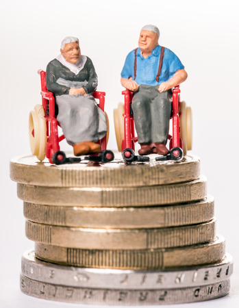 Granny and grandpa in a wheelchair on a money stack Banco de Imagens - 116212925