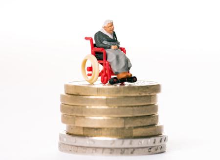 old woman in wheelchair on a money pile Standard-Bild
