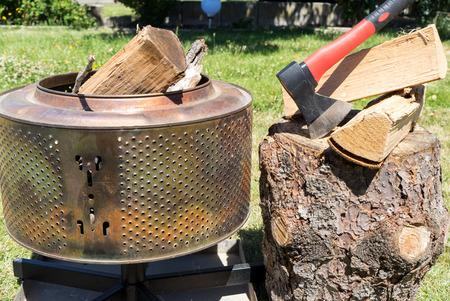 Firewood and an ax in a garden Standard-Bild - 116212965