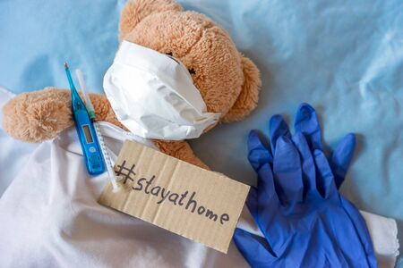 Teddy bear with sign and the words Stay at home