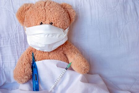 Teddy Bear with face mask and medical thermometer