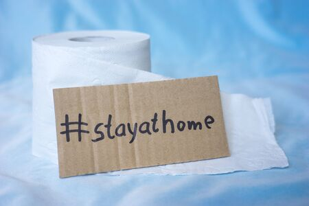 Toilet paper and sign with the words stay at home