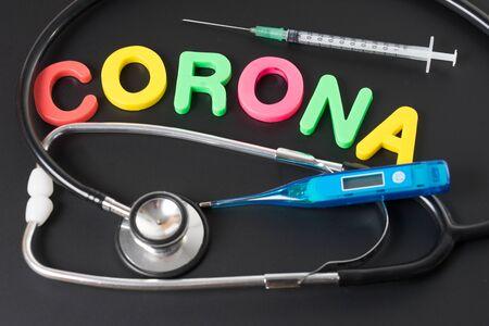 blackboard with the word Corona and stethoscope with syringe