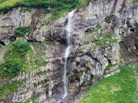 Waterfall Wannenbachfall in the alpine valley of Im Loch - Canton of Glarus, Switzerland
