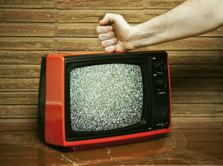 Angry fist hitting broken retro television photo