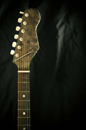 Close up of the neck of a guitar and fret board against a black background.