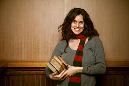 A female college student in the hallyway with her books wearing a green and red scarf set against a wood background.  The woman appears to be happy.